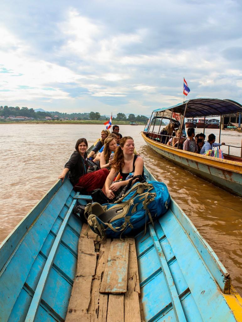 Backpackers får åka longtailbåt till Laos över floden från den Thailändska sidan.