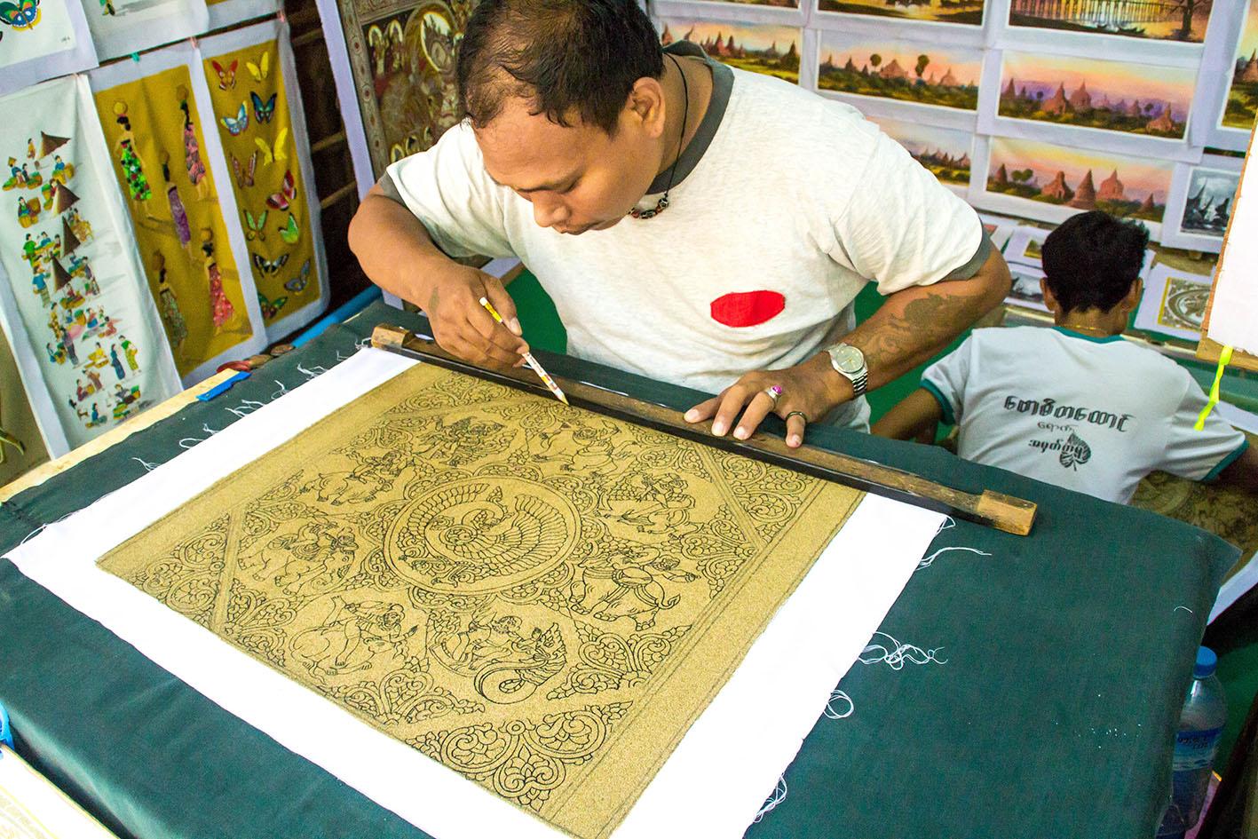 En man skapar mönster på en sandmålning. Den ska så småningom färgläggas och bli till en riktigt vacker tavla.