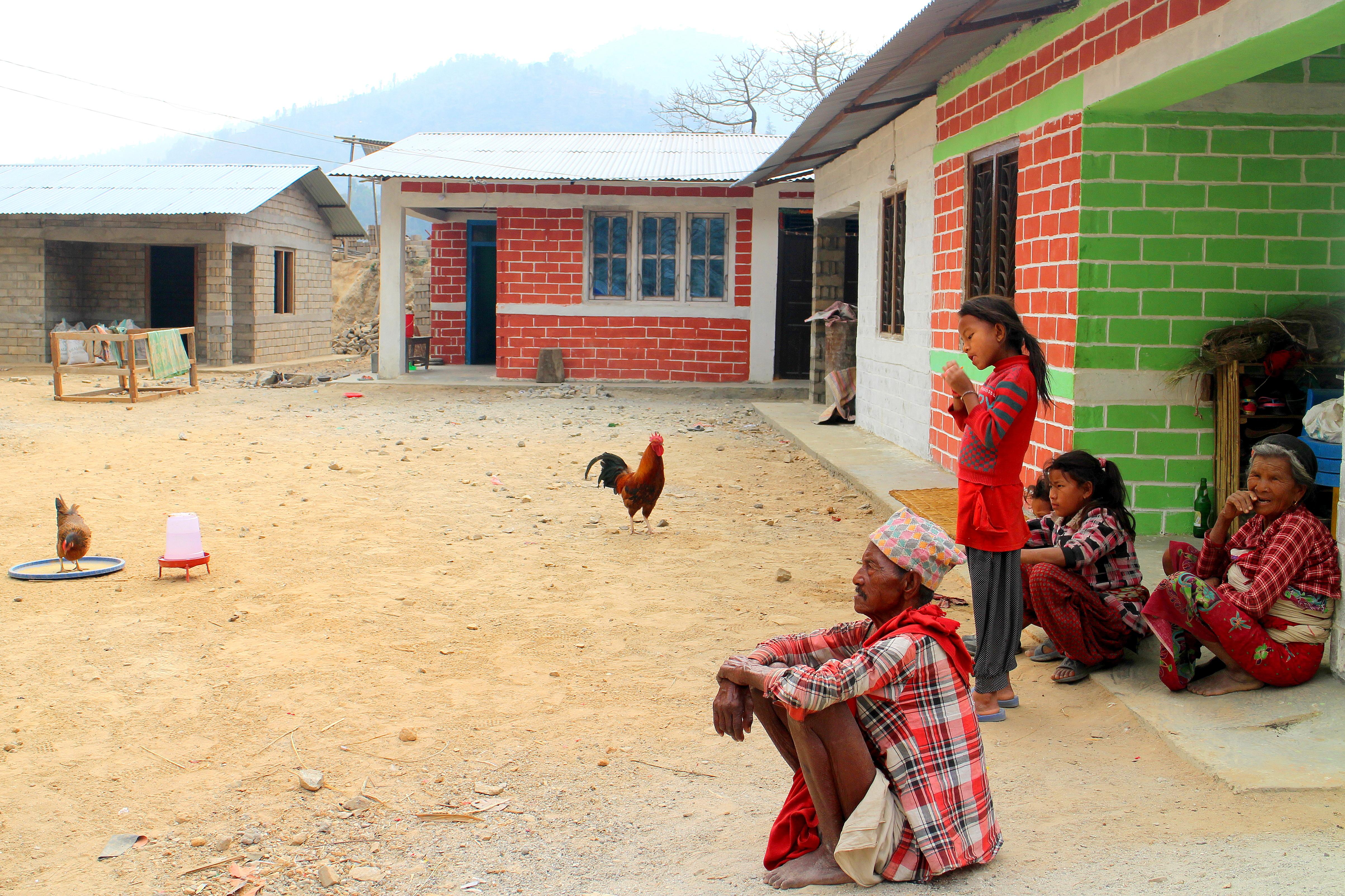Lokalbefolkning i Majhigaun framför sina nybyggda earth brick-hus. Foto: Josefine Nilsson